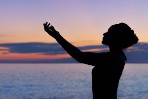 Woman with arms stretched in front of Sunset at Ocean