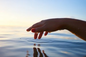 A hand Gently Touches Water