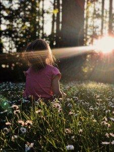 Little girl sits in grass enjoying the Sunset