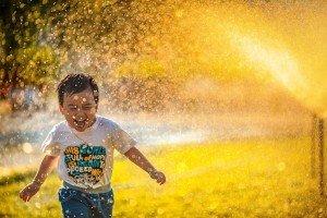 Boy running through Water in the Sun