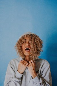 Curly haired woman stands laughing in a hoodie