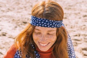 A woman laughing on the beach with red hair