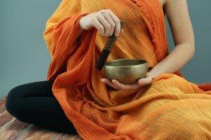 Person Making Sound with a Tibetan Bowl